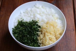 切块洋葱、碎大蒜和碎草药以备refrito或sofrito
