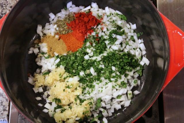 用油炒香洋葱、大蒜、草药和香料,直到洋葱变软