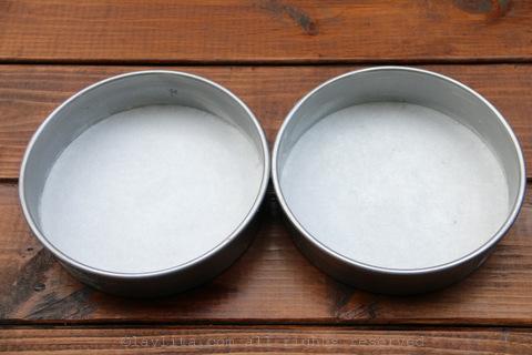 擦油脂和面粉到2个8英寸的圆形蛋糕盘,用烘焙纸排成一行