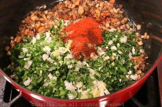 加入切碎的洋葱、大蒜、墨西哥胡椒、红甜椒粉、小茴香和其他香料